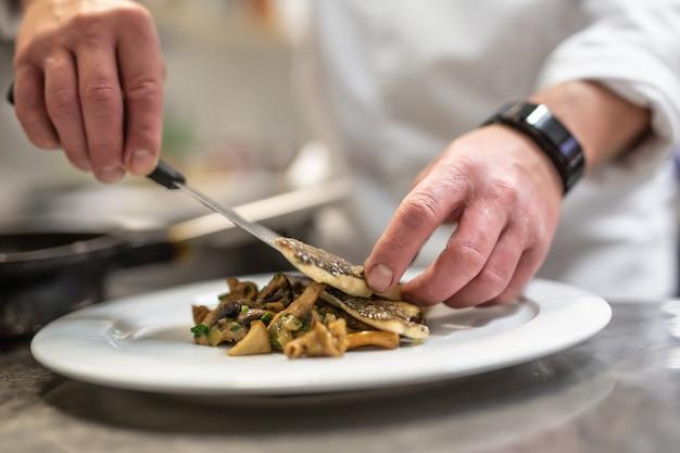 Шеф-повар накрывает рыбу овощами, готовя еду к подаче.