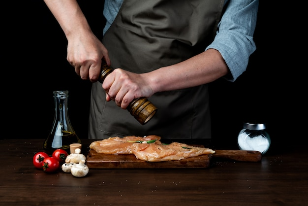 Chef pouring pepper on chicken breast