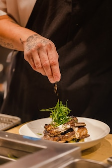 Шеф-повар наливает приправу на говяжий стейк на тарелку