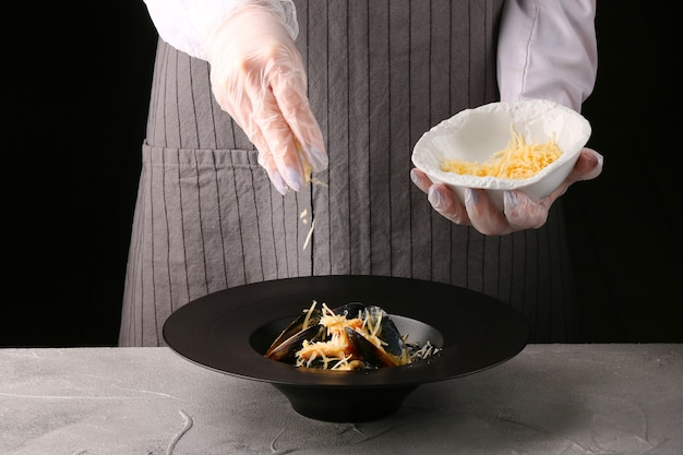 シェフがパスタにチーズを注ぐ。女性シェフ。