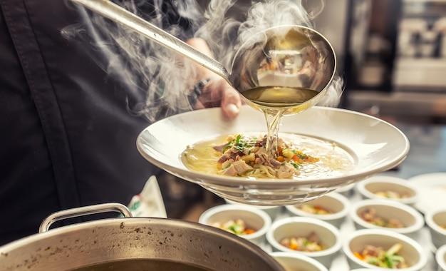 シェフが皿に麺とチキンスープを注ぐ
