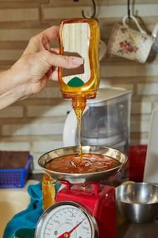 シェフは、サラダに加えるために、ボトルからスケールに蜂蜜を注ぎます。ステップバイステップのレシピ