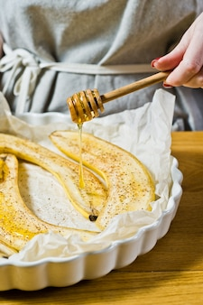 The chef pours honey slices of bananas in a baking dish. cooking baked bananas.