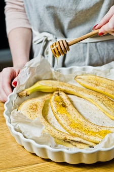 The chef pours honey slices of bananas in a baking dish.