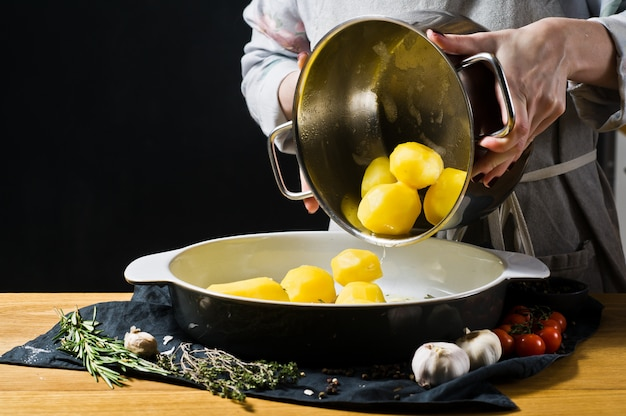 Chef pours potatoes in a baking dish. the concept of cooking baked potatoes.