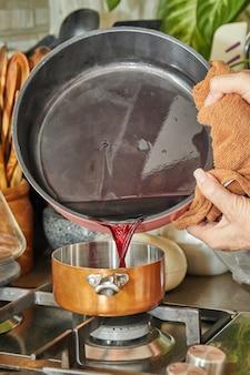 요리사는 소스를 만들기 위해 스토브의 약한 열에 구리 냄비에 액체를 붓습니다.