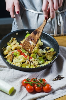 The chef prepares cauliflower and leek in a frying pan.
