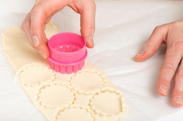 Шеф-повар готовит печенье. женские руки, формочки для печенья и тесто. процесс изготовления домашнего печенья.