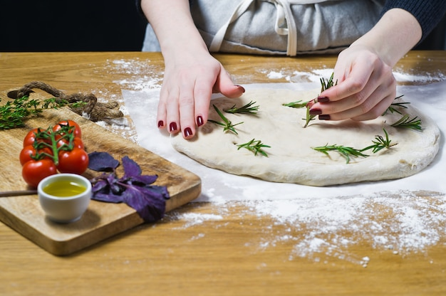 The chef prepares focaccia, lays rosemary on the dough.