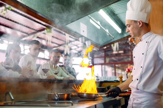 The chef prepares food in front of the visitors in the restaurant