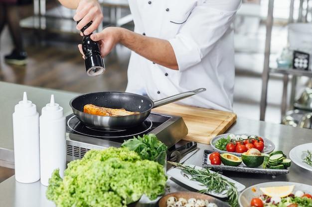 Шеф-повар готовит свежего лосося на профессиональной кухне