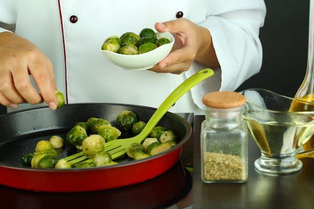 シェフは、調理面のクローズアップで鍋に新鮮な芽キャベツを準備します