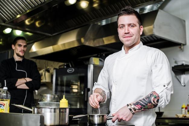 Chef prepares halibut under celery in the restaurant kitchen