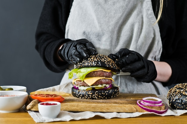 The chef prepares a huge burger. the concept of cooking black cheeseburger.