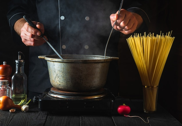 The chef prepares italian pasta on the background of vegetables