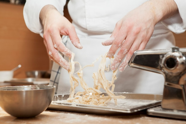 Chef prepares italian traditional fettuccine. close-up of process of cooking fresh homemade pasta.