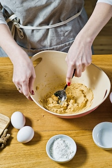 The chef prepares oatmeal cookies, mixes cane sugar and butter. ingredients oat flakes, butter, sugar, eggs, chocolate.