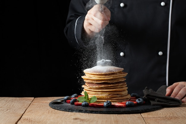 The chef prepares pancakes with berries.