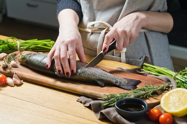 The chef prepares raw trout on a wooden chopping board.