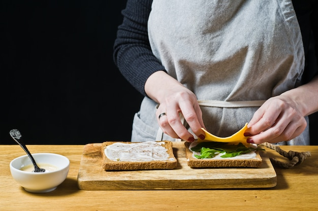 The chef prepares a sandwich of black bread, puts arugula leaves on toast.