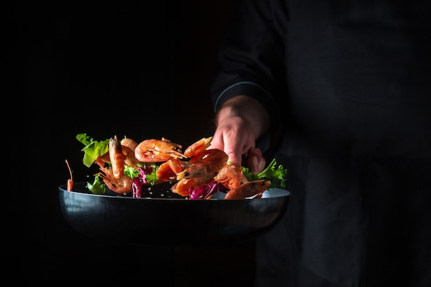 요리사는 허브로 새우를 준비합니다. 어두운 배경에서 해산물, 건강한 채식주의 음식, 음식을 요리하세요. 무료 광고 공간