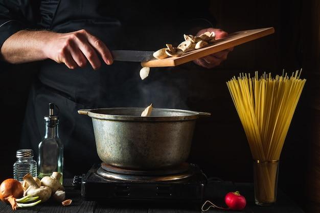 요리사는 야채와 스파게티의 배경에 수프를 준비