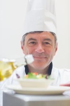 Шеф-повар готовит салат с маслом