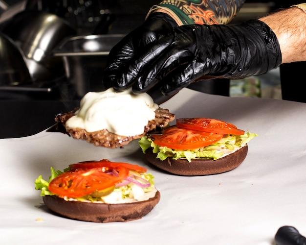 Шеф-повар готовит гамбургер с мясом, котлетой, помидорами, салатом и луком