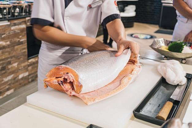 Chef preparing and cutting  fresh salmon in japanese restaurant