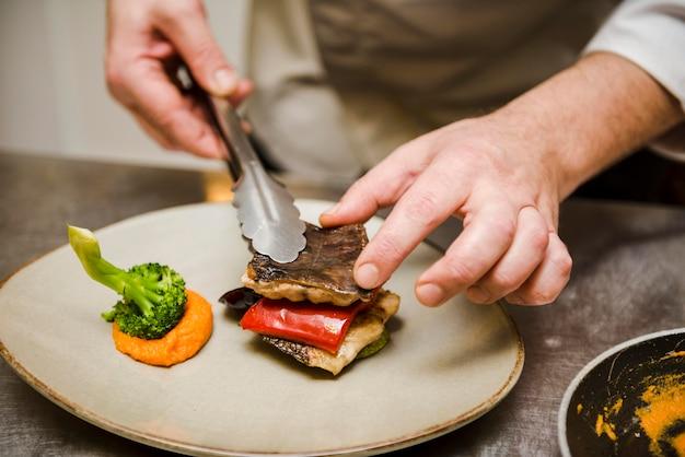 Cuoco unico che prepara alto vicino delizioso del pesce