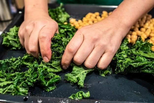 Chef preparing a dish of kale and chickpeas.