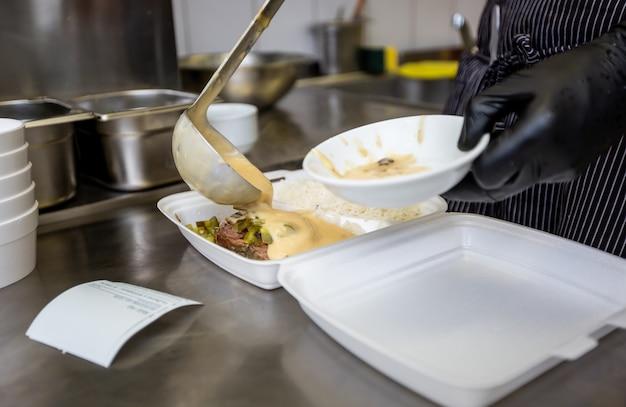 シェフがレストランのボックスに料理を準備し、自宅へのフードデリバリーサービス、オンライン注文