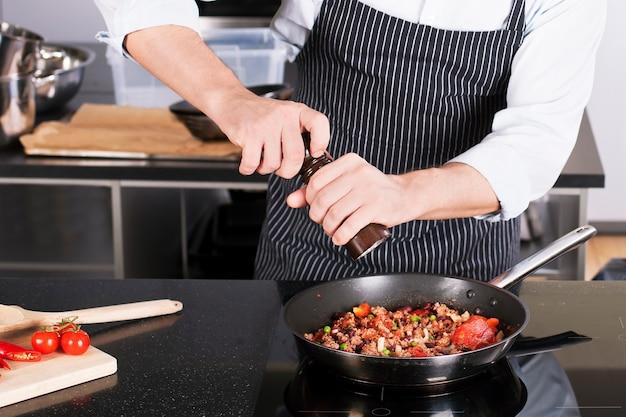フライパンで料理を作るシェフ