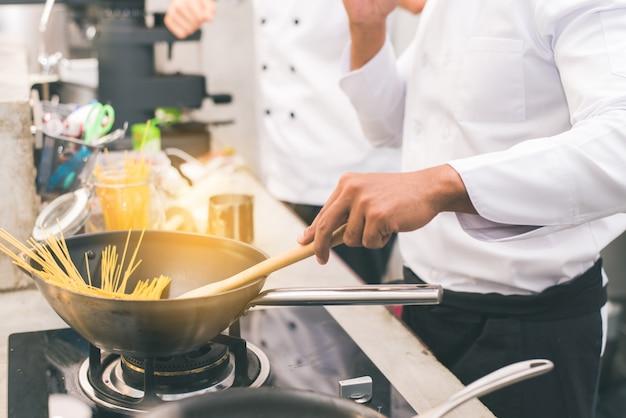 Шеф-повар готовит еду на кухне ресторана