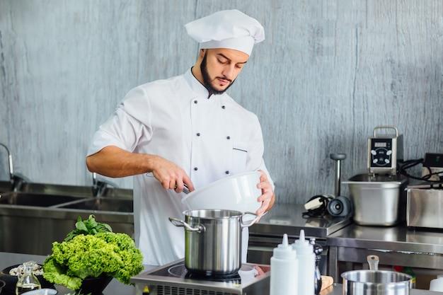 Шеф-повар готовит еду на современной кухне ресторана