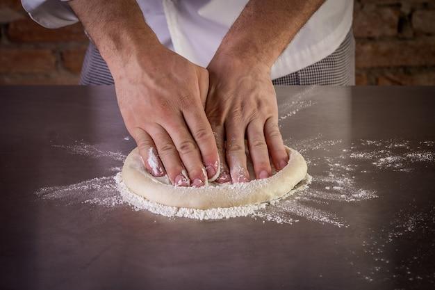 シェフが台所でピザ生地を準備します。