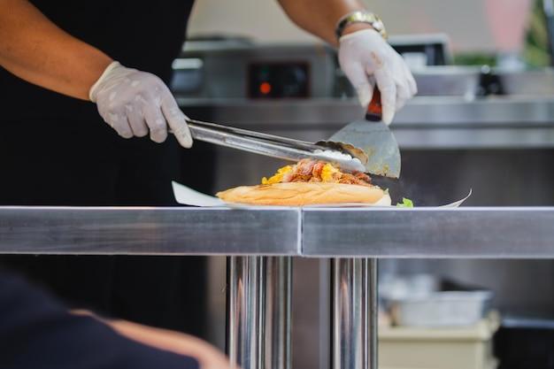Шеф-повар готовит бутерброд на фуд-траке.