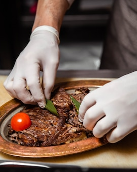 Chef preparing steak platter and adding tomato and oregano leaves.