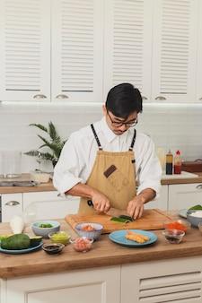 흰색 부엌에 균일 한 슬라이스 재료에 초밥 아시아 마스터 요리사를 준비하는 요리사