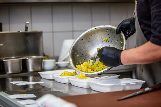 レストランやパブでテイクアウト料理を準備するシェフ、フードデリバリーのコンセプト、宅配、オンライン注文