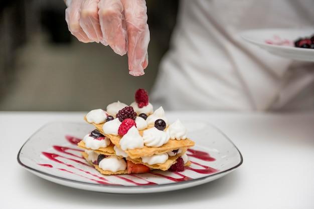 Шеф-повар готовит вкусный десерт крупным планом