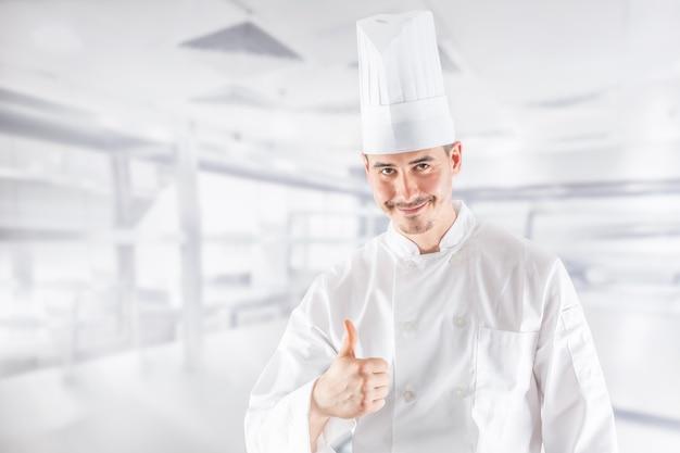 レストランの厨房でプロのシェフが親指を立てる。