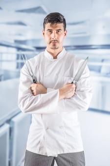 Профессиональный шеф-повар в кухне ресторана, стоя со скрещенными руками и держа вилку и нож.