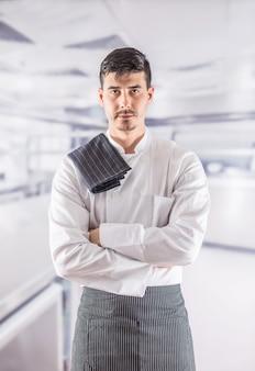 Профессиональный шеф-повар в кухне ресторана, стоя с полотенцем на плече.