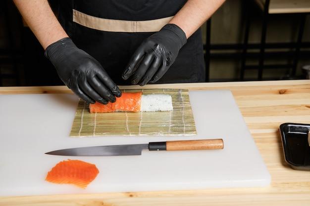 Chef put salmon while preparing rolls