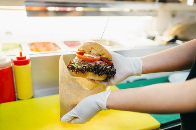 Шеф-повар кладет бургер в картонную упаковку, готовит фаст-фуд. процесс приготовления гамбургера, фастфуд