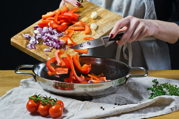 The chef puts chopped red bell peppers and onions with a knife in the pan.