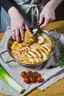 The chef puts the cut chicken breasts in the pan.