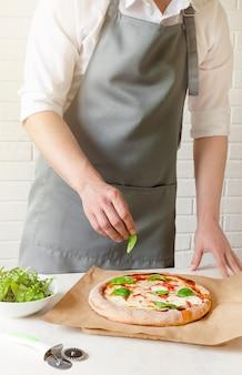 Повар кладет на пиццу зеленые листья базилика.