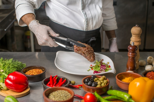 Chef putting grilled steak to the serving plate with herbs salad
